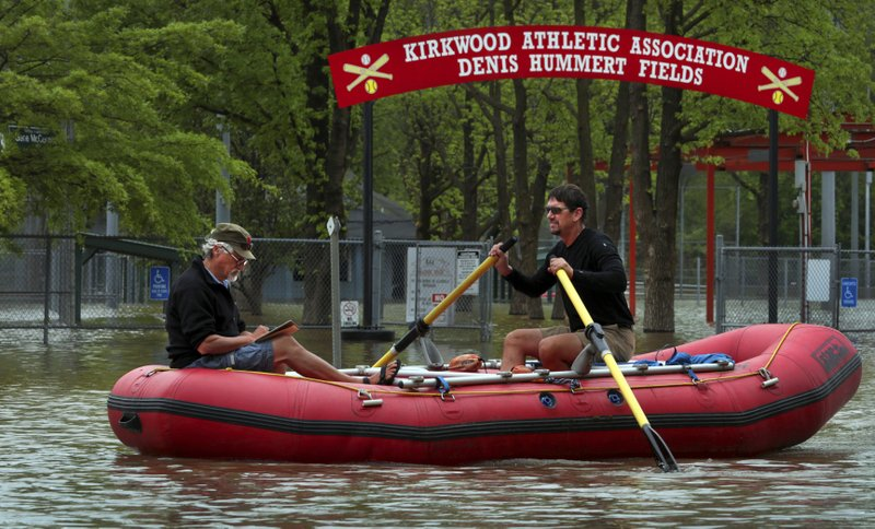 Dan Macheca (right) and Mitch Wieldt get their paddling in as they row along Marshall Road in Meramec River flood water, passing the Kirkwood Athletic Association baseball and softball fields near Greentree Park on Friday, May 3, 2019. The river sits at moderate flood stage but will rise more than four more feet before cresting right at major flood stage early Sunday, an estimated 25.1 feet. The men are training for a 280-mile rafting trip through the Grand Canyon on the Colorado River. (Robert Cohen/St. Louis Post-Dispatch via AP)