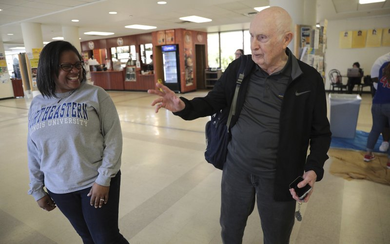 Bob Dwyer, 90, chats with students and staff at Northeastern Illinois University, Wednesday, April 24, 2019. Dwyer will make history Monday when he graduates from Northeastern Illinois University, becoming the school's oldest student to receive his bachelor's degree since the school started keeping such records in 1962. (Antonio Perez/Chicago Tribune via AP)