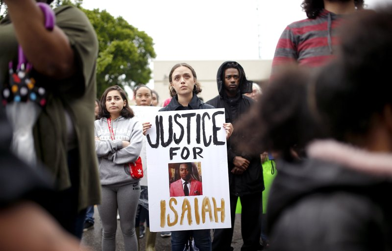 A protestor holds a sign at the Edmond Police Department during a Black Lives Matter protest rally honoring the life of Isaiah Lewis in Edmond, Okla., Friday, May 3, 2019. Police in the Oklahoma City suburb of Edmond said that Isaiah Lewis, a naked 17-year-old high school student was not armed when he was fatally shot by police after breaking into a home.(Sarah Phipps/The Oklahoman via AP)