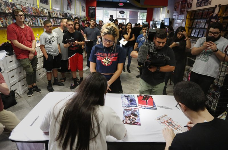 A large group of fans gather to get autographs from Steve Aoki during a comic book signing of his new