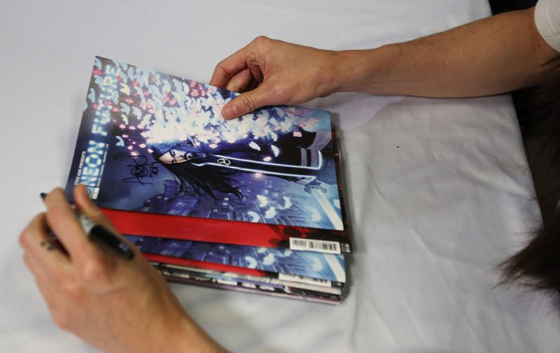 Steve Aoki holds and signs his comic book during a signing of his new