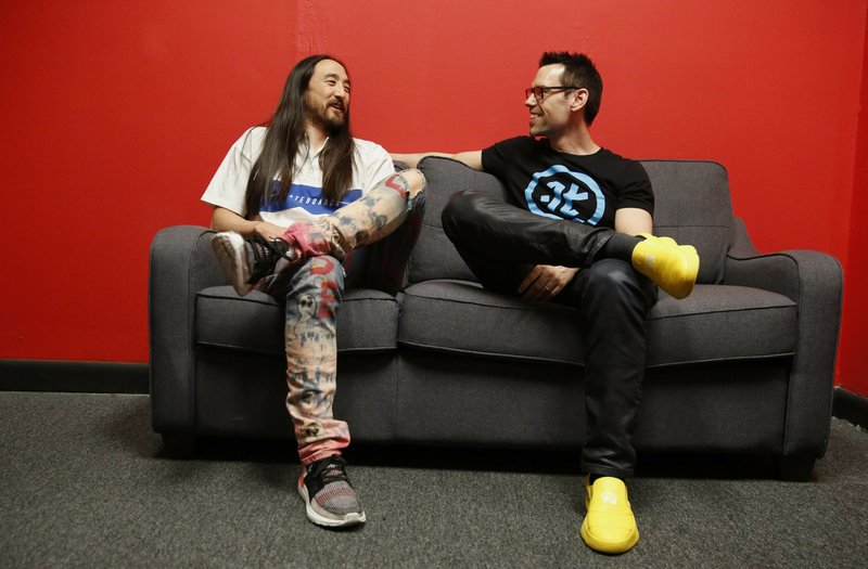 Steve Aoki, left, and Tom Bilyeu, right, sit for a portrait during a comic book signing of his new comic book series