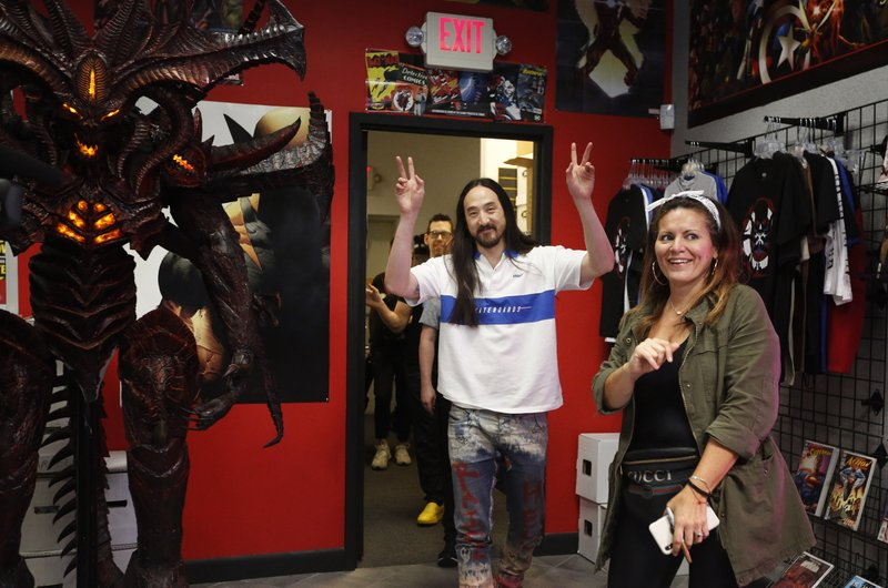 Steve Aoki, center, gestures to his fans as he enters a comic book signing of his new