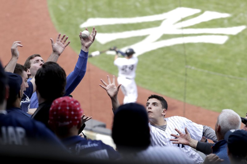 A fan barehands a foul ball hit by New York Yankees' Luke Voit during the sixth inning of a baseball game against the Minnesota Twins, Saturday, May 4, 2019, in New York. (AP Photo/Julio Cortez)