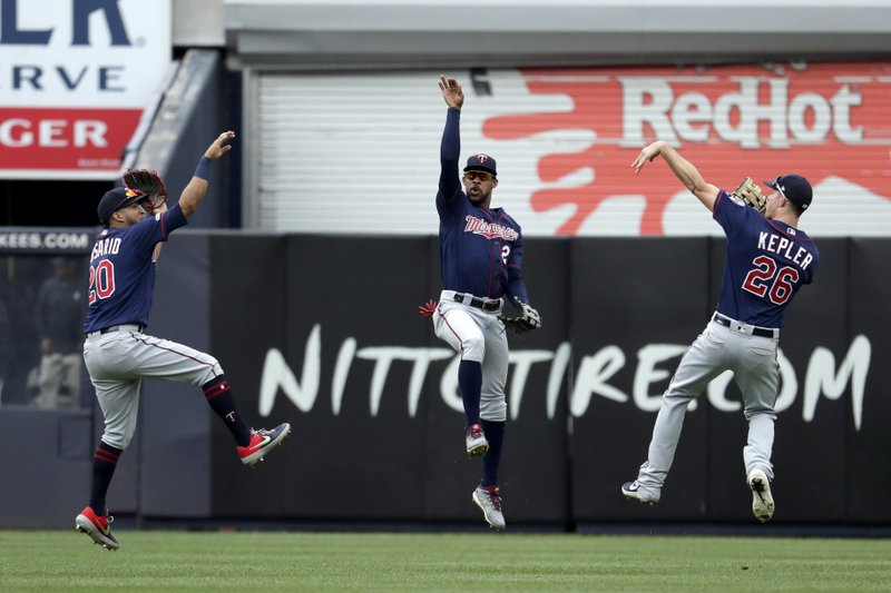 Minnesota Twins left fielder Eddie Rosario (20), center fielder Byron Buxton (25) and right fielder Max Kepler (26) celebrate after defeating the New York Yankees in a baseball game, Saturday, May 4, 2019, in New York. (AP Photo/Julio Cortez)