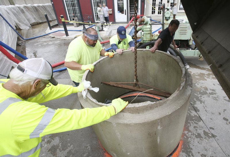 Alton, Illinois, Public Works employees place a concrete section of storm sewer pipe over a manhole cover on the dry side of a 6-foot-high flood wall Friday, May 3, 2019, at the foot of State Street in downtown Alton, Ill. The pipe will help contain floodwaters that are backing up through the storm sewer system. The wall, left, is made of many 3,200-pound concrete blocks, and was erected Tuesday, May 2, 2019, to hold back Mississippi River floodwaters from the downtown business district. (John Badman/The Telegraph via AP)