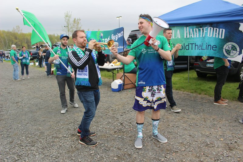 Hartford Athletic fan Myke Furhman, of New Fairfield, Conn., plays his coronet in the parking lot of Rentschler Field in East Hartford, Conn., Saturday, May 4, 2019, prior to the USL Championship soccer team's inaugural home game, while Mike Peshka, of Southington, Conn., holds a megaphone. (AP Photo/Pat Eaton-Robb)