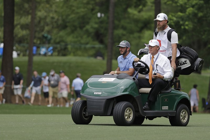 Max Home, left, is driven down the 10th fairway after play was halted for weather in the area during the third round of the Wells Fargo Championship golf tournament at Quail Hollow Club in Charlotte, N.C., Saturday, May 4, 2019. (AP Photo/Chuck Burton)
