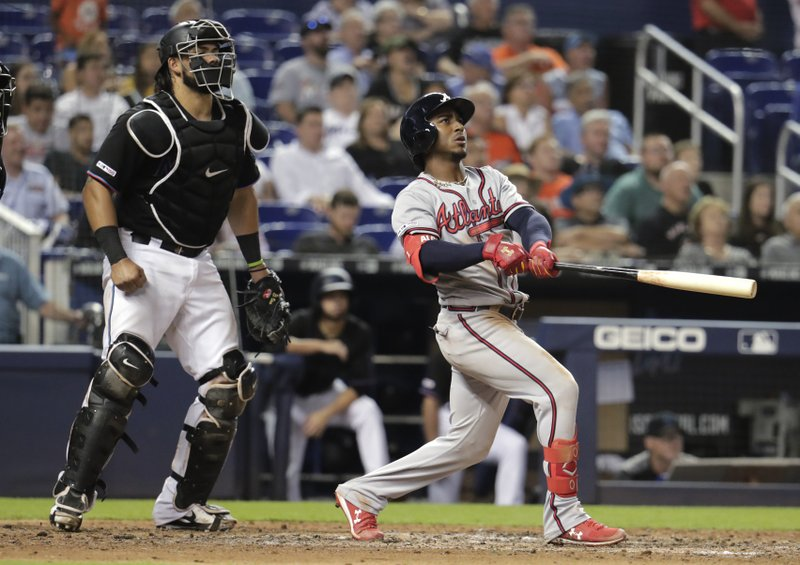 Atlanta Braves' Ozzie Albies, right, watches his grand slam during the sixth inning of the team's baseball game against the Miami Marlins, Saturday, May 4, 2019, in Miami. At left is Marlins catcher Jorge Alfaro. (AP Photo/Lynne Sladky)