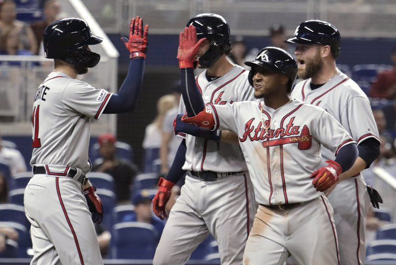 Atlanta Braves' Ozzie Albies, right, is congratulated at the plate by Ender Inciarte, left, after hitting a grand slam during the sixth inning of the team's baseball game against the Miami Marlins, Saturday, May 4, 2019, in Miami. (AP Photo/Lynne Sladky)