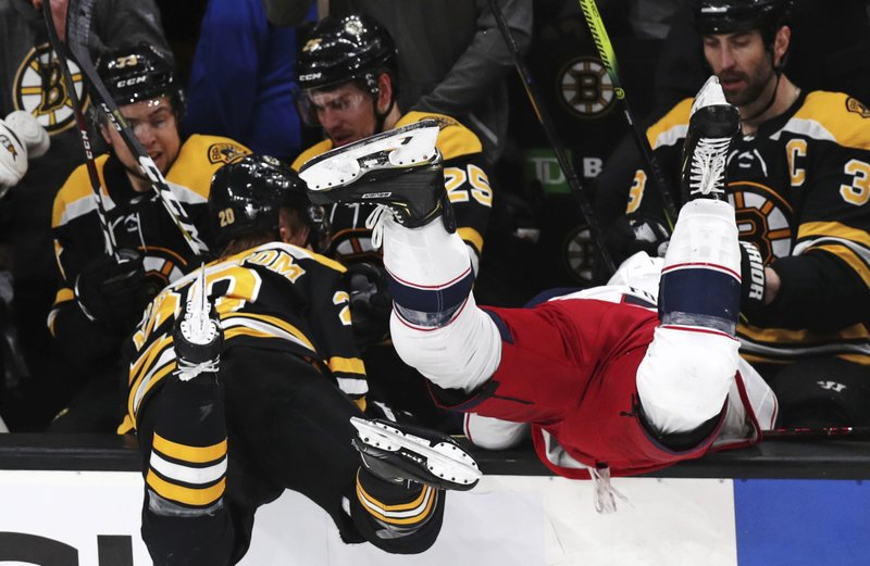 Columbus Blue Jackets left wing Nick Foligno, right, is checked into the Boston Bruins bench by Bruins center Joakim Nordstrom, left, during the first period of Game 5 of an NHL hockey second-round playoff series, Saturday, May 4, 2019, in Boston. (AP Photo/Charles Krupa)
