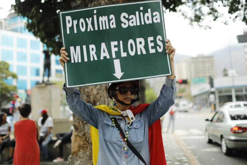 An opponent to Venezuela's President Nicolas Maduro holds a sign reading in Spanish