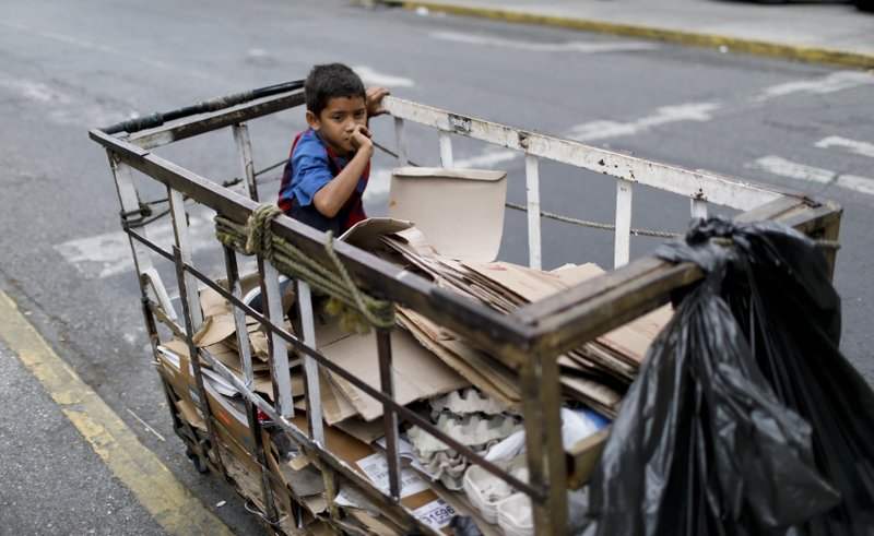 A boy sits in a recycler's cart in Caracas, Venezuela, Saturday, May 4, 2019. (AP Photo/Ariana Cubillos)