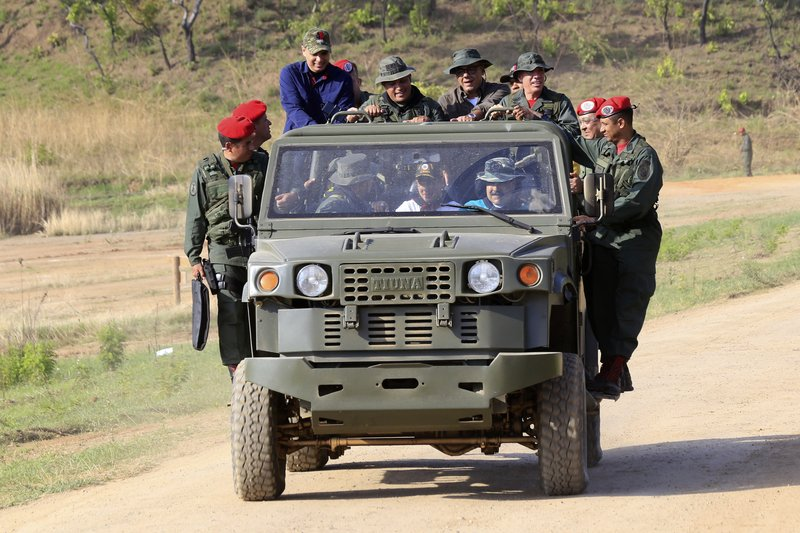 In this handout photo released by Miraflores Press Office, Venezuela's President Nicolas Maduro drives a military vehicle at the G/J José Laurencio Silva training center in the state of Cojedes, Venezuela, Saturday, May 4, 2019. (Jhonn Zerpa/Miraflores Press Office via AP)