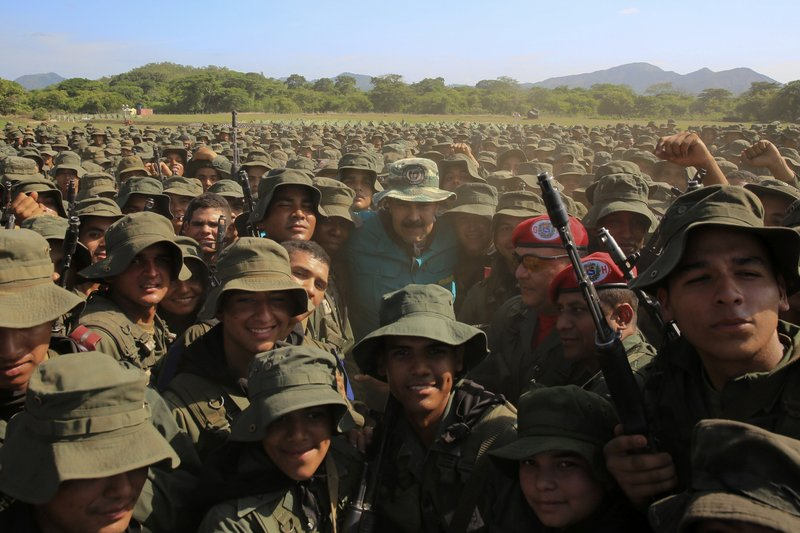 In this handout photo released by Miraflores Press Office, Venezuela's President Nicolas Maduro poses for a group photo with cadets at the G/J José Laurencio Silva training center in the state of Cojedes, Venezuela, Saturday, May 4, 2019. (Jhonn Zerpa/Miraflores Press Office via AP)