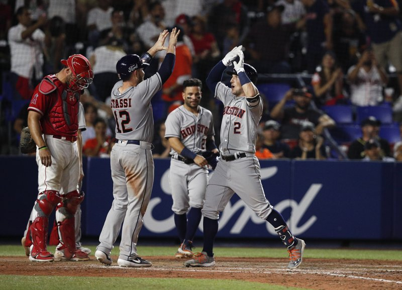 Houston Astros' Alex Bregman, right, is congratulated by teammate Max Stassi, as he runs home after hitting a home run in the eighth inning of a baseball game against the Los Angeles Angels, in Monterrey, Mexico, Saturday, May 4, 2019. (AP Photo/Rebecca Blackwell)