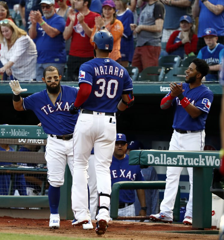 Texas Rangers' Rougned Odor, left, and Elvis Andrus, right, celebrate with Nomar Mazara at the dugout entrance following Mazara's solo home run against the Toronto Blue Jays during the first inning of a baseball game in Arlington, Texas, Saturday, May 4, 2019. (AP Photo/Tony Gutierrez)