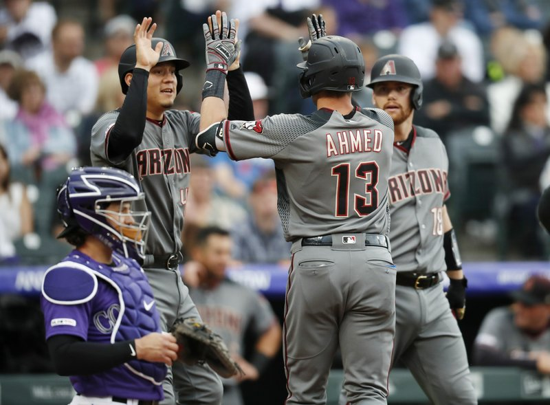 Arizona Diamondbacks' Nick Ahmed, front right, is congratulated by Wilmer Flores, back left, and Carson Kelly after hitting a two-run home run off Colorado Rockies starting pitcher Kyle Freeland in the second inning of a baseball game Saturday, May 4, 2019, in Denver. Rockies catcher Tony Wolters, front left, looks on. (AP Photo/David Zalubowski)