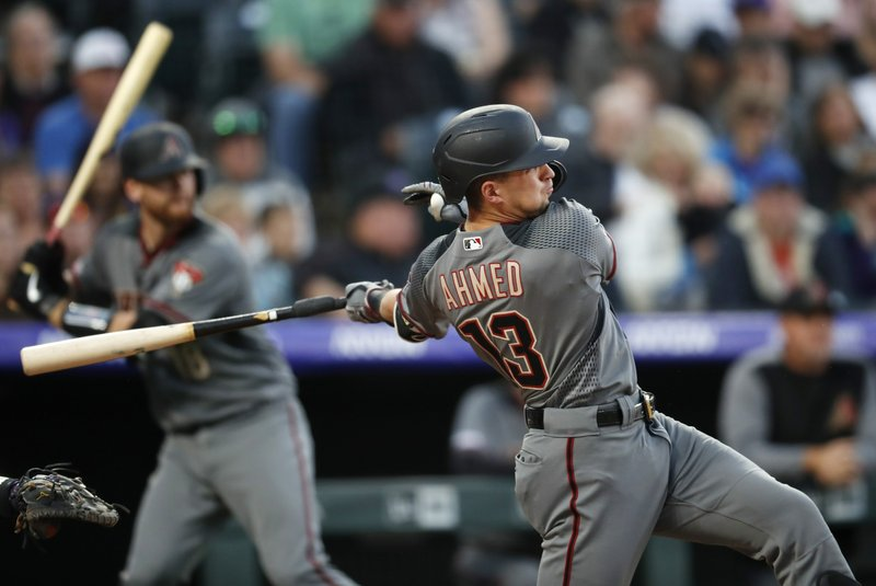 Arizona Diamondbacks' Nick Ahmed follows through with his swing after connecting for a double against Colorado Rockies starting pitcher Kyle Freeland in the sixth inning of a baseball game Saturday, May 4, 2019, in Denver. (AP Photo/David Zalubowski)