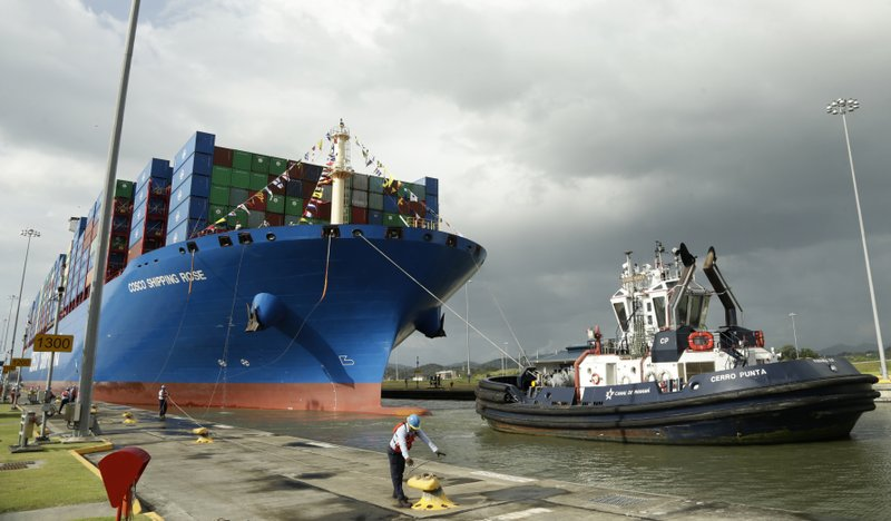 FILE - In this Dec. 3, 2018 file photo, a Panama Canal worker docks the Chinese container ship Cosco at the Panama Canal's Cocoli Locks. Panama remains a strategic location for commerce, anchored by the heavily trafficked Panama Canal shipping route and a recently expanded international airport. (AP Photo/Arnulfo Franco, File)