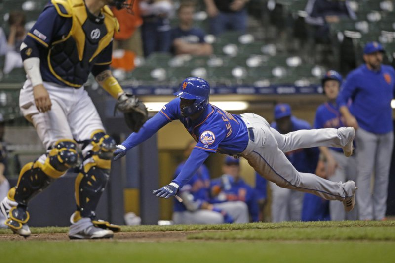 New York Mets' Adeiny Hechavarria scores against the Milwaukee Brewers during the 18th inning of a baseball game Saturday, May 4, 2019, in Milwaukee. (AP Photo/Jeffrey Phelps)