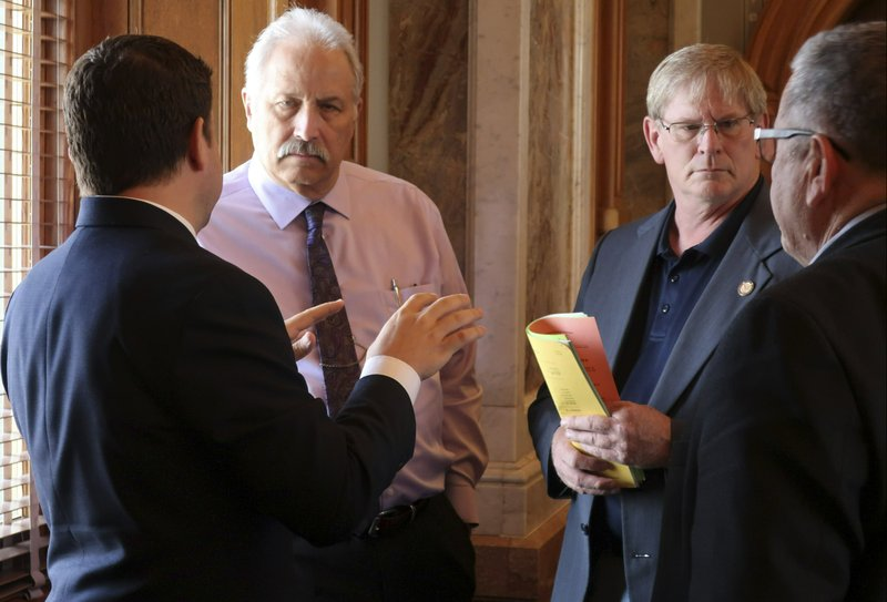 Republican members of the Kansas House confer as they wait for a vote on a proposed state budget, Saturday, May 4, 2019, at the Statehouse in Topeka, Kan. They are, from left to right, Reps. J.R. Claeys, R-Salina; John Resman, R-Olathe; Leo Delperdang, R-Wichita, and Emil Bergquist, R-Wichita. (AP Photo/John Hanna)