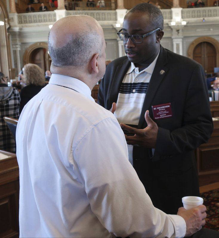 Kansas state Rep. K.C. Ohaebosim,, D-Wichita, right, confers with House Minority Leader Tom Sawyer, also D-Wichita, while the House waits for a debate on a proposed budget, Saturday, May 4, 2019, at the Statehouse in Topeka, Kan. Democrats and moderate Republicans were holding up the budget in the House in hopes of forcing a debate on Medicaid expansion in the Senate. (AP Photo/John Hanna)