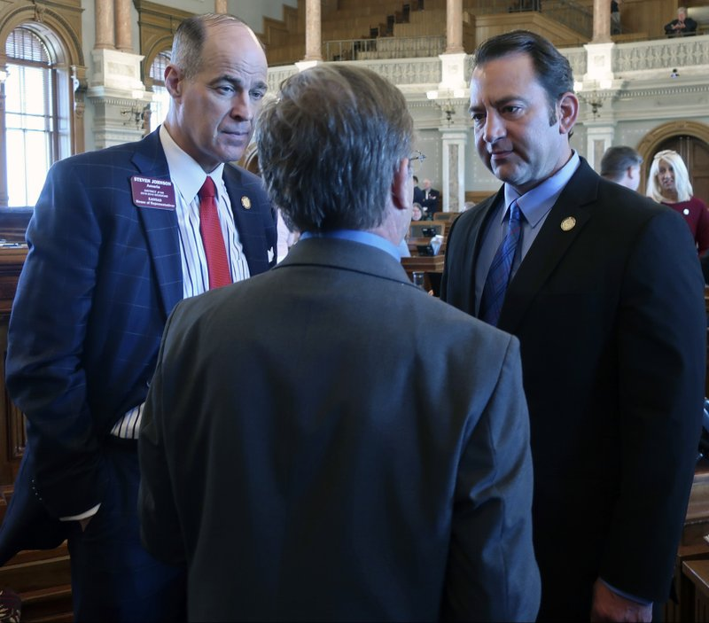 Kansas House Taxation Committee Chairman Steven Johnson, left, R-Assaria, and Appropriations Committee Chairman Troy Waymaster, right, R-Bunker Hill, talk to Rep. Jene Vickrey, R-Louisburg, during a break in the House's session, Saturday, May 4, 2019, at the Statehouse in Topeka, Kan. The Legislature's Republican leaders were trying to break an impasse over the budget and Medicaid expansion. (AP Photo/John Hanna)