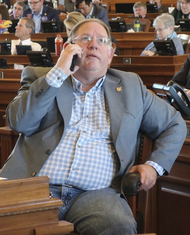 Kansas House Majority Leader Dan Hawkins, R-Wichita, talks on his cell phone and watches a vote-tallying board as the House passes a proposed state budget at the Statehouse Saturday, May 4, 2019, in Topeka, Kan. The budget passed after an effort to block it in hopes of forcing a debate on Medicaid expansion collapsed. (AP Photo/John Hanna)