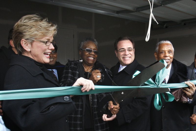 FILE- In this Jan. 18, 2010, file Sallie Sanders, second from left, is helped by then Michigan Gov. Jennifer Granholm, left, former Wayne County Executive Robert Ficano and Judge Damon Keith with a ribbon cutting outside her new house in Hamtramck, Mich. Nearly 50 years after her family was forced out of their rental house, Sanders cut the ribbon to a new home in the city _ the remedy in one of the longest-running cases of housing discrimination in the United States. (AP Photo/Carlos Osorio, File)