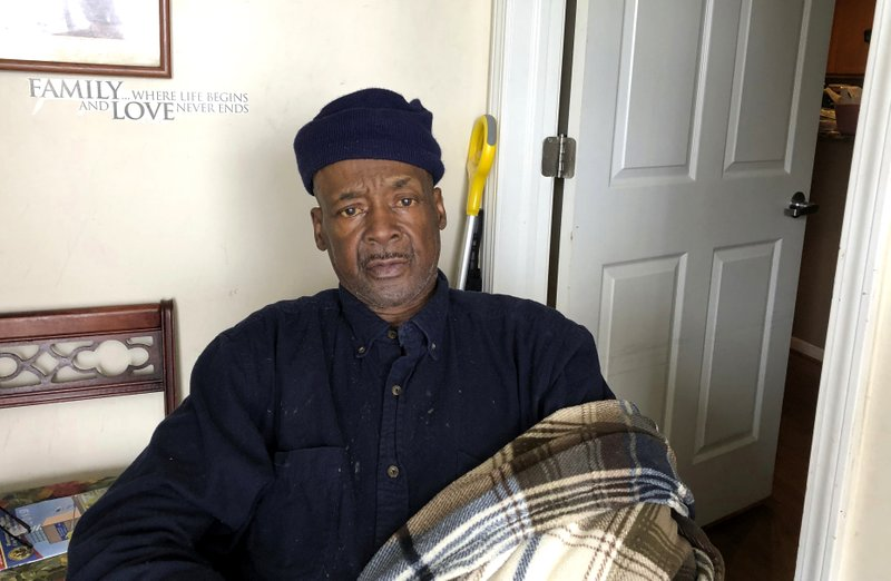 In this May 2, 2019, photo Lemuel Sawyer, 61, poses for a photo in his home in Hamtramck, Mich., which he moved into in 2014. Hamtramck agreed to build 200 units of single-family housing as a remedy for destroying black neighborhoods in the 1960s. Three houses still remain to be built, decades after Hamtramck was found liable for racial discrimination. Federal Judge Damon Keith recently died at age 96 without seeing the end of the case. (AP Photo/Ed White)