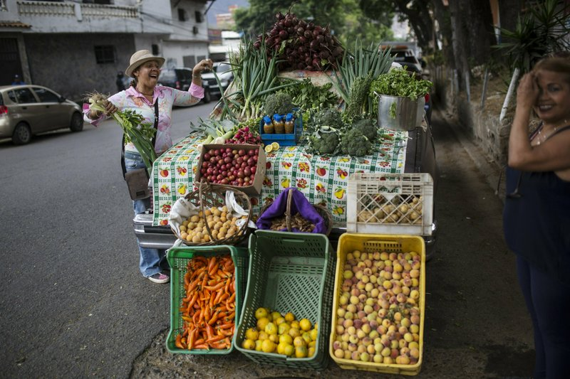 Nancy Espinoza, 55, who uses an old car as her stand, sells vegetables to a customer in Caracas, Venezuela, Friday, May 3, 2019. (AP Photo/Rodrigo Abd)