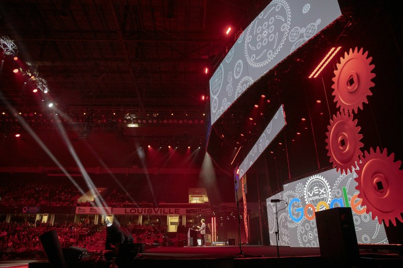 In this Thursday, April 25, 2019 photo, gears, video boards, and spotlights don the stage as the emcee begins announcing participating countries at the VEX World Robotics Championships in Louisville Ky. (Michelle Hutchins/Courier Journal via AP)