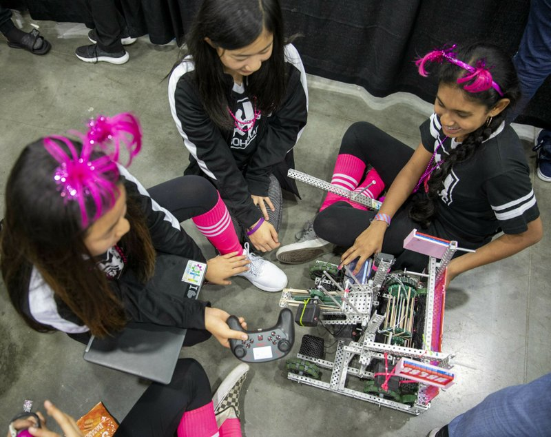 In this Thursday, April 25, 2019 photo, Seventh and eighth graders Amisha Chandra, Elina Kim, Olivia Ramirez, Kristina Tu, of the Orchard Hills, Calif RoboHawks team wait in the practice queue to start off the VEX World Robotics Championships in Louisville Ky. (Michelle Hutchins/Courier Journal via AP)