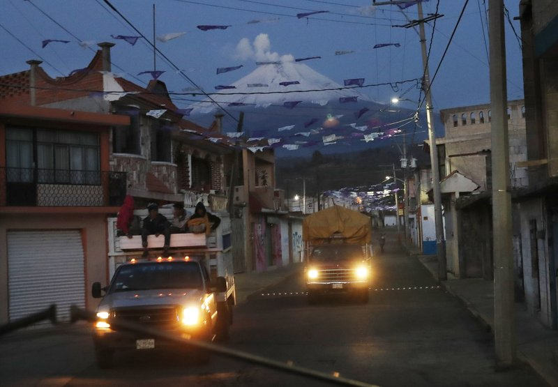 In this Friday, May 3, 2019 photo, drive through the streets in village Santiago Xalitzintla, Mexico as the Popocatepetl volcano spews ash nearby. The Mexican village has the distinction of being the community closest to Popocatépetl, a crater that has increasingly been belching lava and spewing ash as far as Mexico City, 90 kilometers (56 miles) to the northwest. (AP Photo/Marco Ugarte)