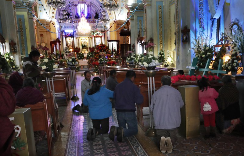 In this Thursday, May 2, 2019 photo, residents kneel in prayer marking the Day of the Holy Cross celebrations, mixing Catholic traditions with pre-Hispanic rituals and beliefs. in the village Santiago Xalitzintla, Mexico. The Day of the Holy Cross is a religious holiday celebrated in many parts of Latin America that marks Byzantine Empress Saint Helena's search for the cross on which Jesus was crucified. (AP Photo/Marco Ugarte)