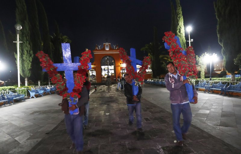 In this Thursday, May 2, 2019 photo, pilgrims arrive with crosses adorned with red flowers marking the Day of the Holy Cross celebrations, mixing Catholic traditions with pre-Hispanic rituals and beliefs. in the village Santiago Xalitzintla, Mexico. The Day of the Holy Cross is a religious holiday celebrated in many parts of Latin America that marks Byzantine Empress Saint Helena's search for the cross on which Jesus was crucified. (AP Photo/Marco Ugarte)
