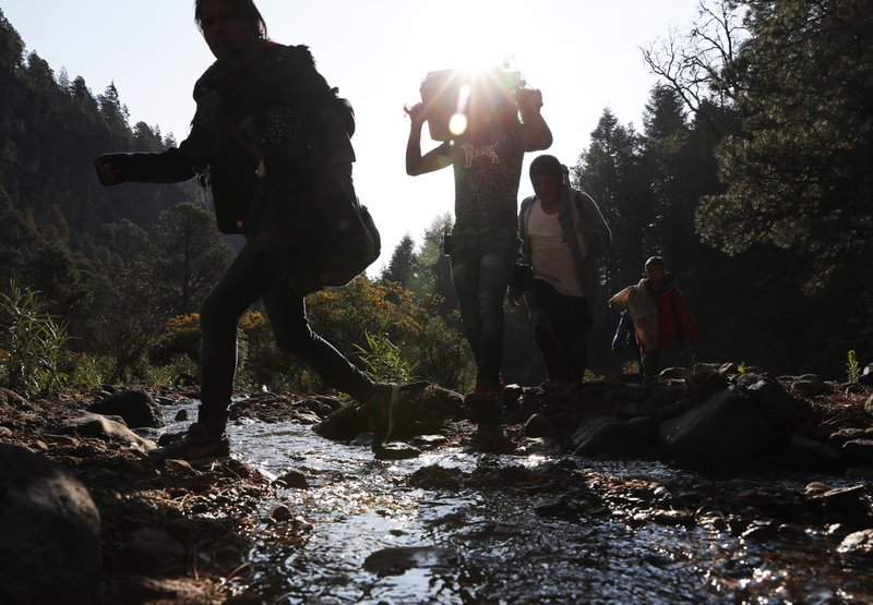In this Friday, May 3, 2019 photo, pilgrims hike to an altar on the flanks of the Iztaccíhuatl volcano or The Sleeping Woman (the volcano resembles a reclining female), as part of the Day of the Cross celebrations, near Santiago Xalitzintla, Mexico. Residents celebrate over two days in early May, and leave offerings on an altar at the base of the volcano, asking for a good harvest and as gratitude for harvests past. (AP Photo/Marco Ugarte)