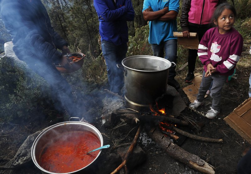 In this Friday, May 3, 2019 photo, residents cook communal meals over open fires on the flanks of the Iztaccíhuatl volcano or The Sleeping Woman (the volcano resembles a reclining female), as part of the Day of the Cross celebrations,  near Santiago Xalitzintla, Mexico. The residents of Santiago Xalitzintla celebrate over two days in early May, and leave offerings on an altar at the base of the volcano, asking for a good harvest and as gratitude for harvests past. (AP Photo/Marco Ugarte)