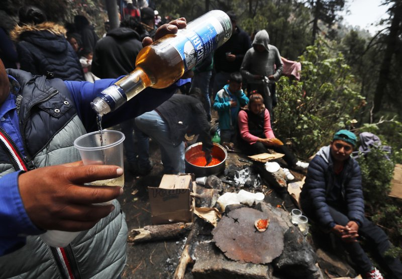 In this Friday, May 3, 2019 photo, a celebrant pours liquor into a plastic cup on the flanks of the Iztaccíhuatl volcano or The Sleeping Woman (the volcano resembles a reclining female), as part of the Day of the Cross celebrations,  near Santiago Xalitzintla, Mexico. The residents of Santiago Xalitzintla celebrate over two days in early May, and leave offerings on an altar at the base of the volcano, asking for a good harvest and as gratitude for harvests past. (AP Photo/Marco Ugarte)