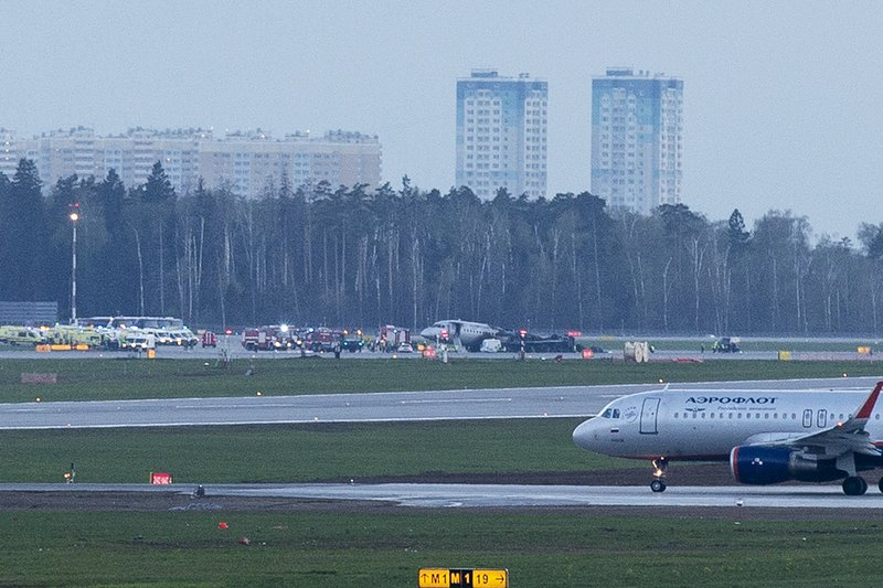 The Sukhoi SSJ-100 aircraft of Aeroflot Airlines, center, is seen after an emergency landing in Sheremetyevo airport in Moscow, Russia, Sunday, May 5, 2019. The plane belonging to Russian national carrier Aeroflot landed in flames at the airport. (AP Photo/Alexander Zemlianichenko)
