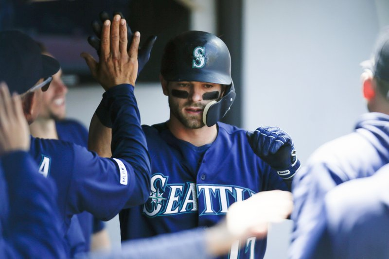 Seattle Mariners' Mitch Haniger celebrates in the dugout after hitting a solo home run off Cleveland Indians relief pitcher Jon Edwards during the second inning of a baseball game, Sunday, May 5, 2019, in Cleveland. (AP Photo/Ron Schwane)
