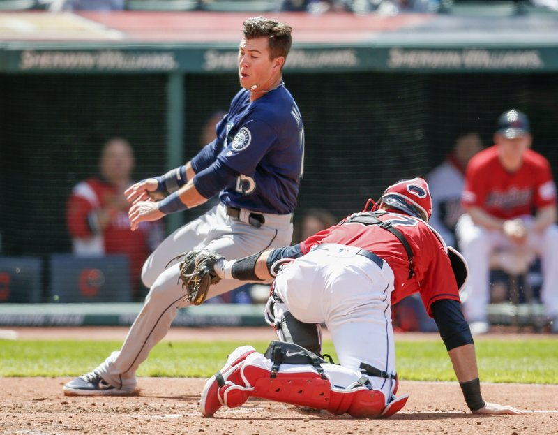 Seattle Mariners' Dylan Moore (25) scores past Cleveland Indians' Kevin Plawecki (27) on a single by Braden Bishop during the fifth inning of a baseball game, Sunday, May 5, 2019, in Cleveland. (AP Photo/Ron Schwane)