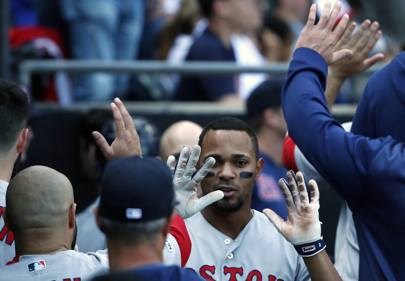 Boston Red Sox's Xander Bogaerts celebrates in the dugout with teammates after hitting a grand slam during the eighth inning of a baseball game against the Chicago White Sox in Chicago Sunday, May 5, 2019. (AP Photo/Jeff Haynes)