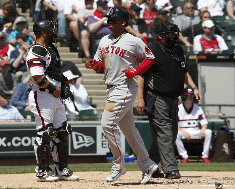Boston Red Sox's Rafael Devers, center, scores in front of Chicago White Sox catcher Welington Castillo, left, and umpire Fieldin Culbreth during the second inning of a baseball game in Chicago Sunday, May 5, 2019. (AP Photo/Jeff Haynes)