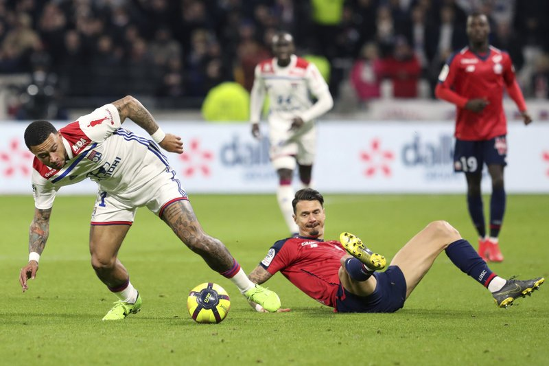 Lyon's Memphis Depay, left, challenges for the ball with Lille's Jose Miguel Da Rocha Fonte, right, during a French League One soccer match in Decines, near Lyon, central France, Sunday, May 5, 2019. (AP Photo/Laurent Cipriani)