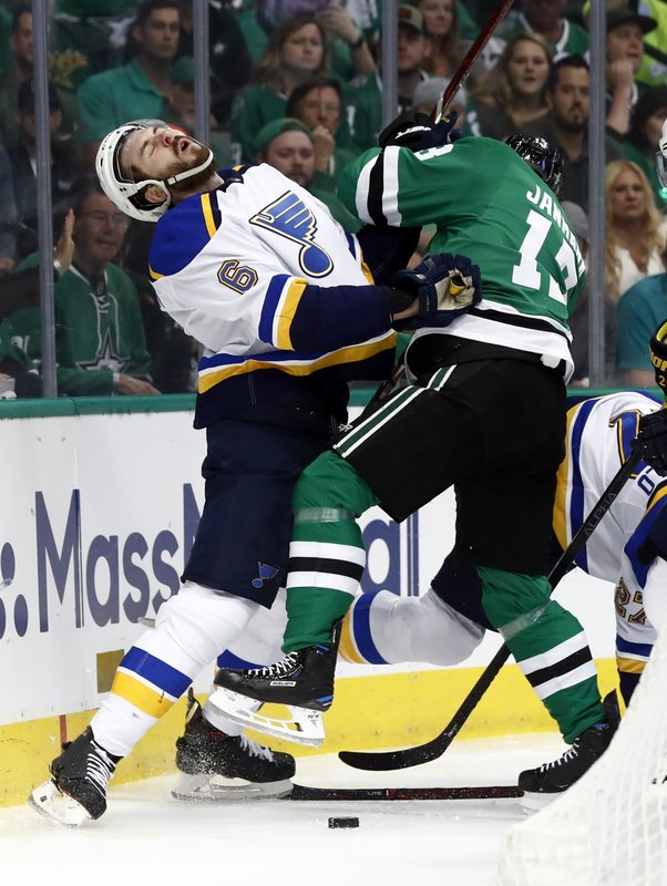St. Louis Blues' Joel Edmundson (6) recoils after being hit by Dallas Stars' Mattias Janmark, of Sweden, while fighting for control of a loose puck along the boards during the first period in Game 6 of an NHL second-round hockey playoff series, Sunday, May 5, 2019, in Dallas. (AP Photo/Tony Gutierrez)