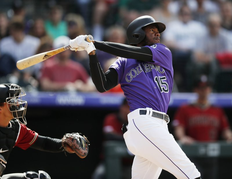 Colorado Rockies' Raimel Tapia follows the flight of his triple to drive in three runs off Arizona Diamondbacks relief pitcher Archie Bradley in the eighth inning of a baseball game Sunday, May 5, 2019, in Denver. (AP Photo/David Zalubowski)