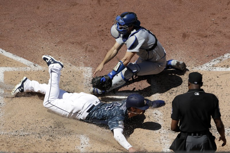 The San Diego Padres' Wil Myers, bottom left, scores off a sacrifice fly by Francisco Mejia as Los Angeles Dodgers catcher Austin Barnes, top, is late with the tag during the fourth inning of a baseball game Sunday, May 5, 2019, in San Diego. (AP Photo/Gregory Bull)