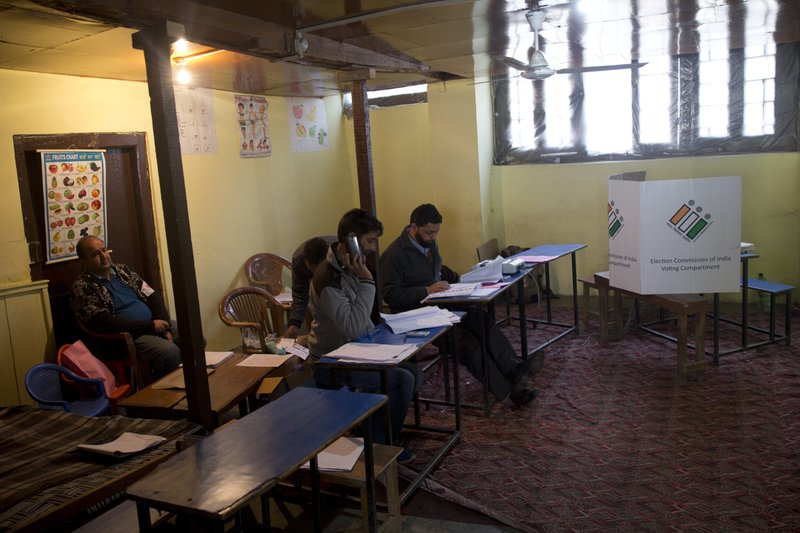 FILE - In this April 18, 2019, file photo, election officers sit inside an empty polling station during the second phase of India's general elections, in Srinagar, Indian controlled Kashmir, as Kashmiri separatist leaders have called for a boycott of the vote. (AP Photo/ Dar Yasin)